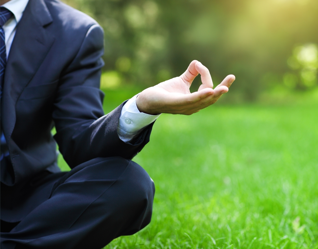 Business man relaxing in a park in the lotus position. Close up